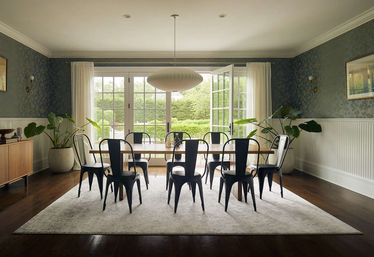 A large dining room table topped with a very small centerpiece