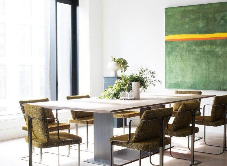 A contemporary dining room table surrounded by olive green chairs