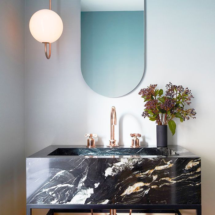 Bathroom with black marble sink and copper fixtures, globe pendant light