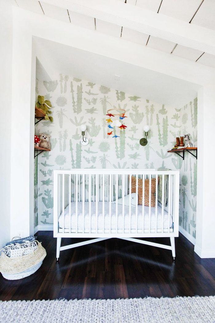 nursery with crib and cacti wallpaper