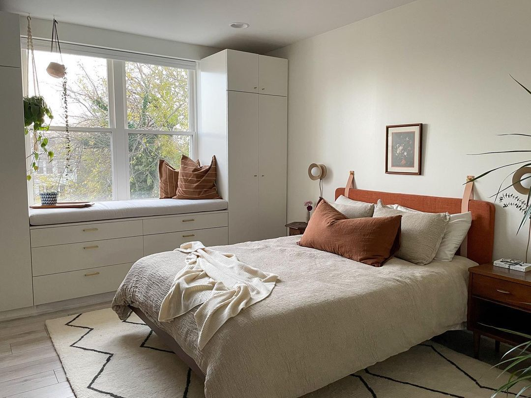 Neutral bedroom with warm terracotta colored pillows.