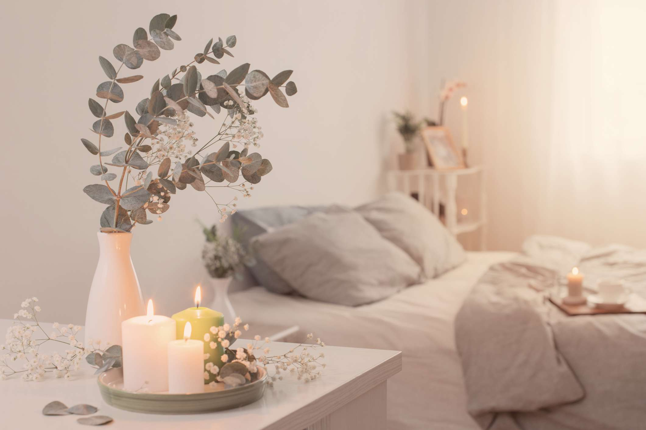 cozy bedroom with candles on bedside table