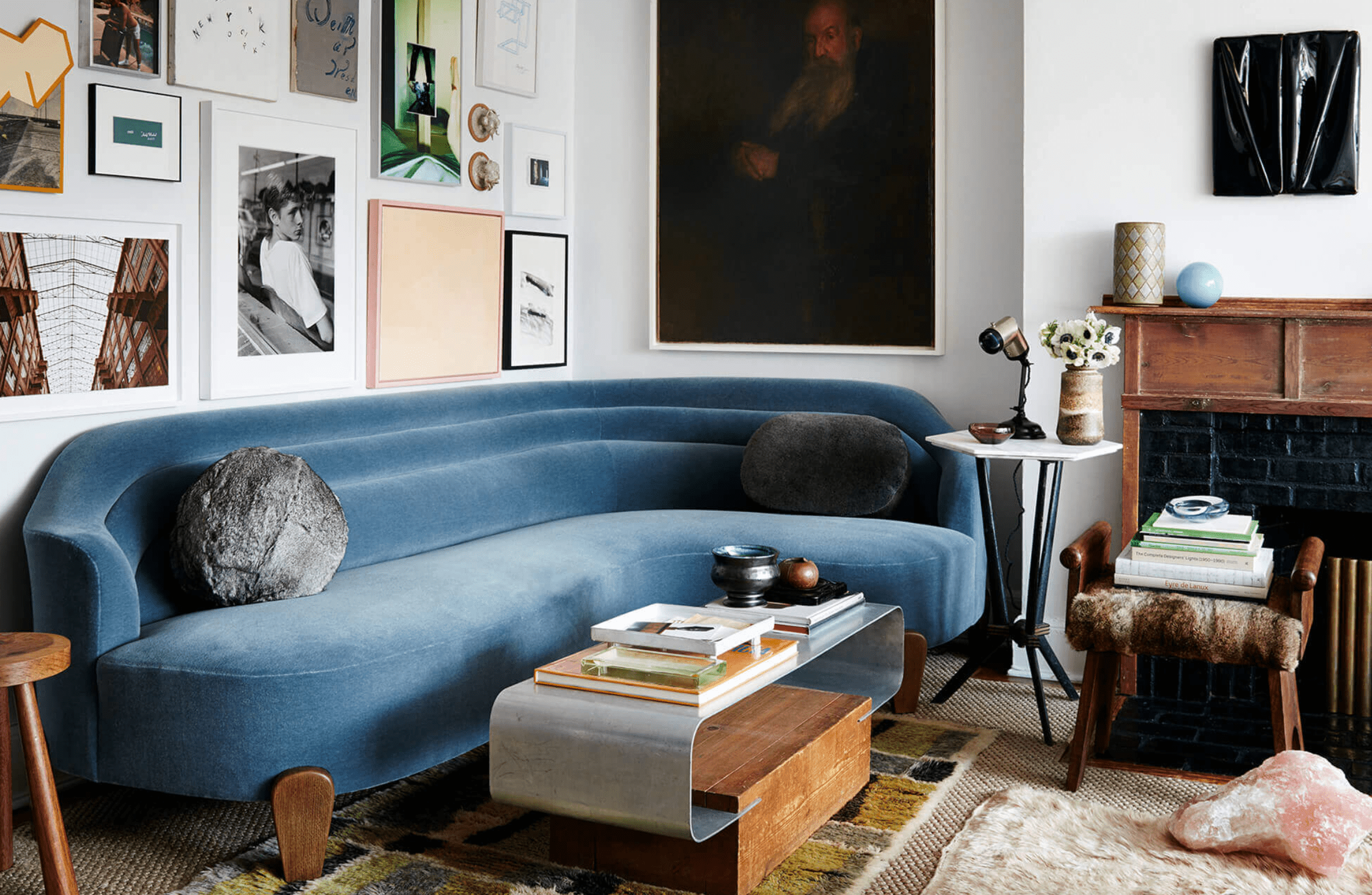 A living room with a sleek blue couch, several tables, and a small upholstered stool being used as a table