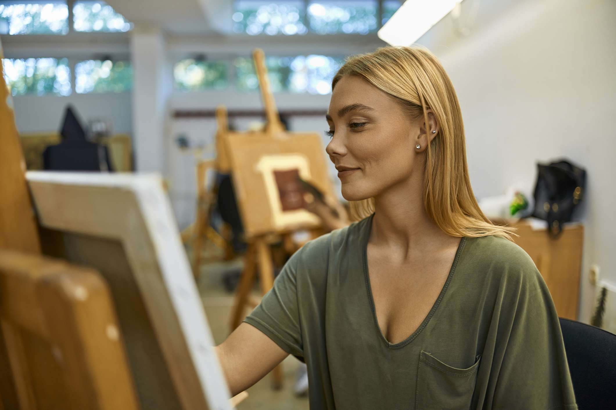 Woman paints on canvas in art class
