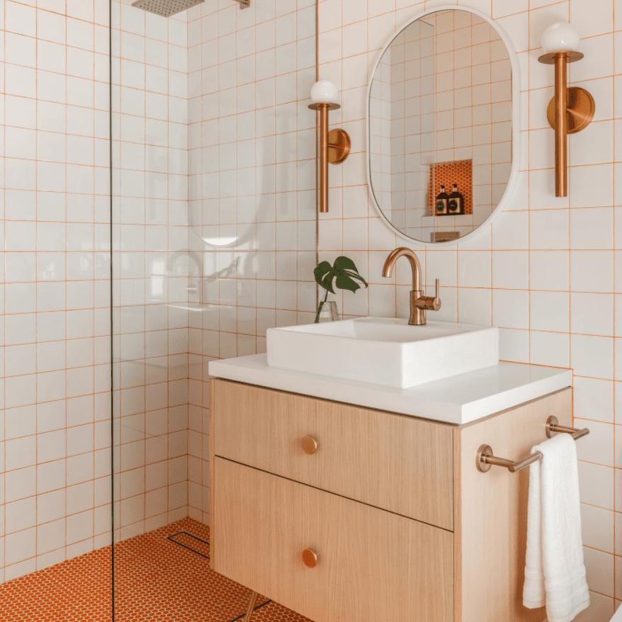A bathroom lined with white tiles and orange grout