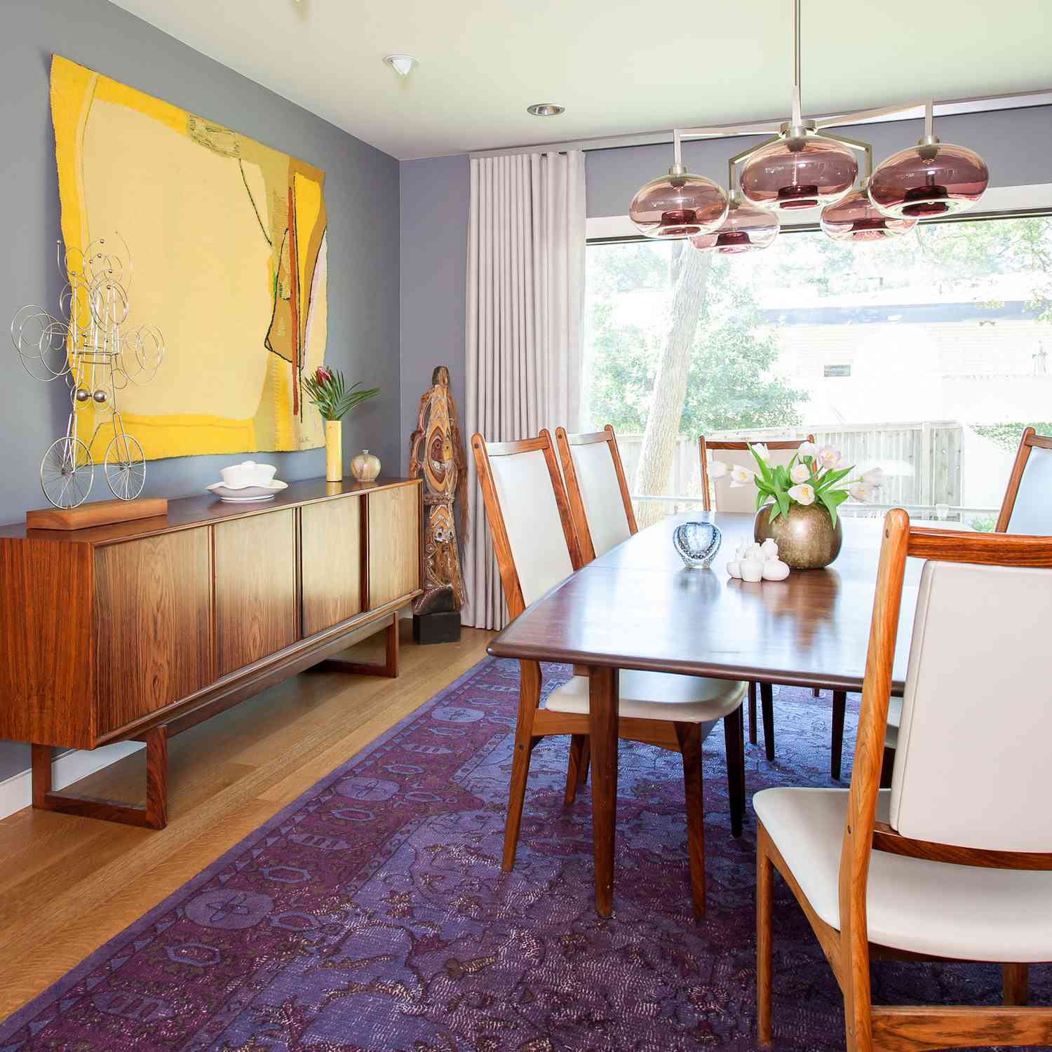 A colorful dining room with blue-gray walls, yellow art, a dark pint chandelier, and a striking purple rug