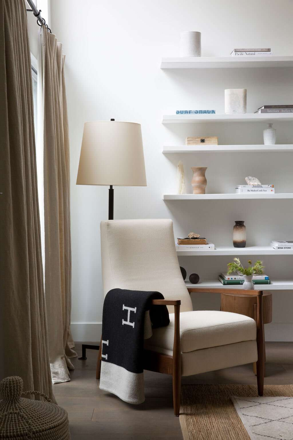 Styled corner with arm chair, open shelves, and initialed blanket