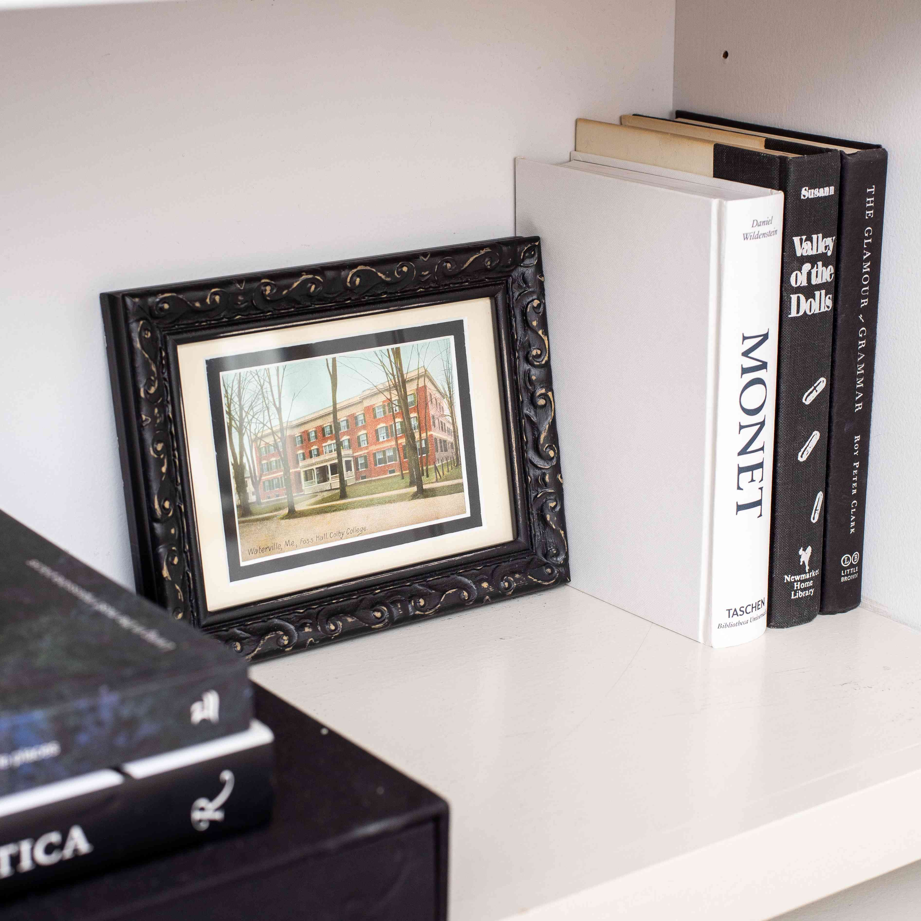 Small frame next to hardcover books.