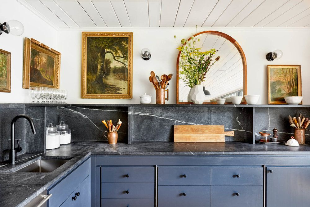 A kitchen with blue cabinets, black marble countertops, and art-covered walls