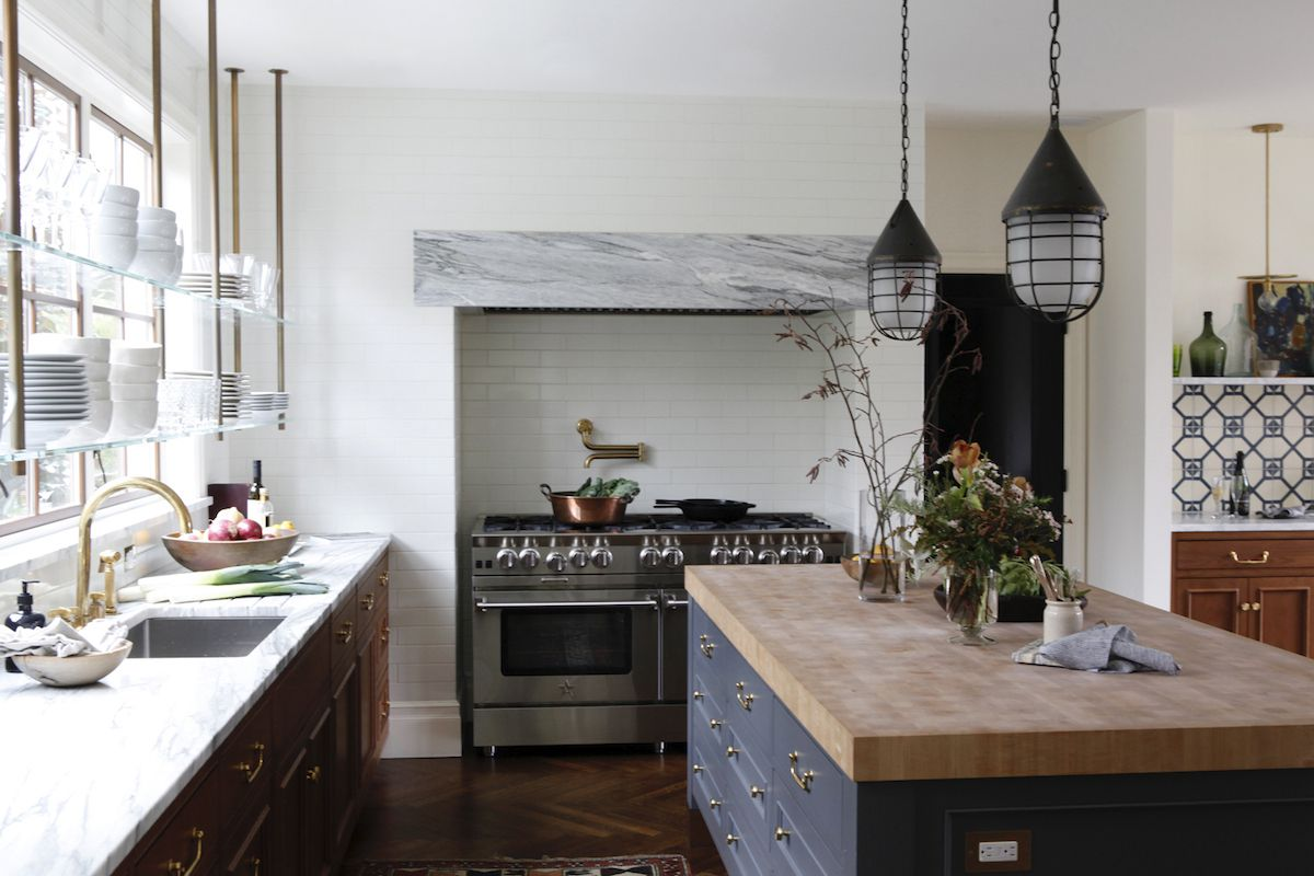 A kitchen filled with mixed-and-matched cabinets, countertops, and lighting fixtures