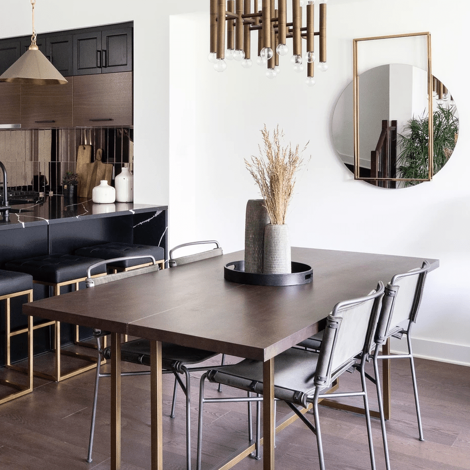 A sleek dining room table with a couple centerpieces stored inside a round tray
