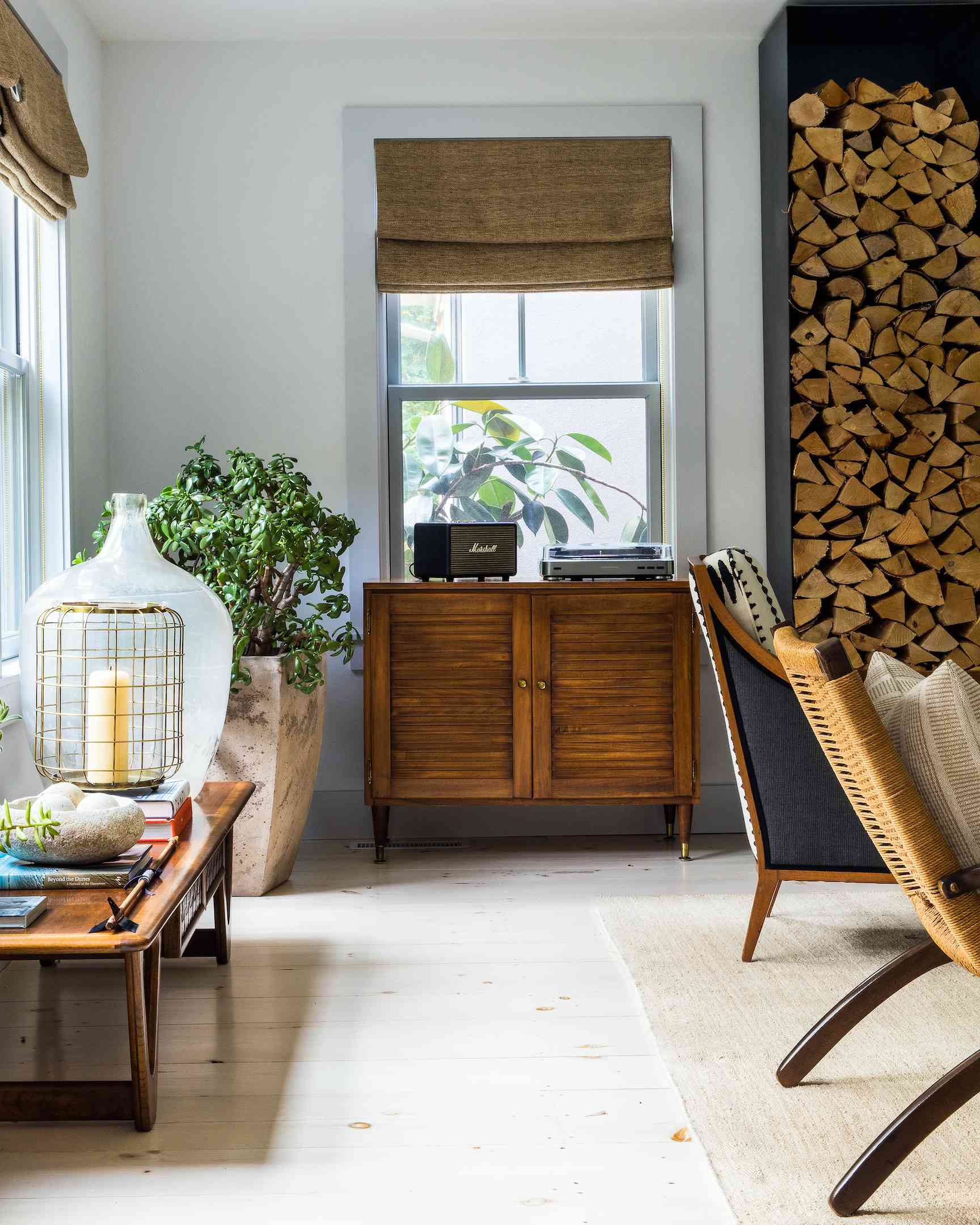 Living room with stack of wood and wooden dresser.