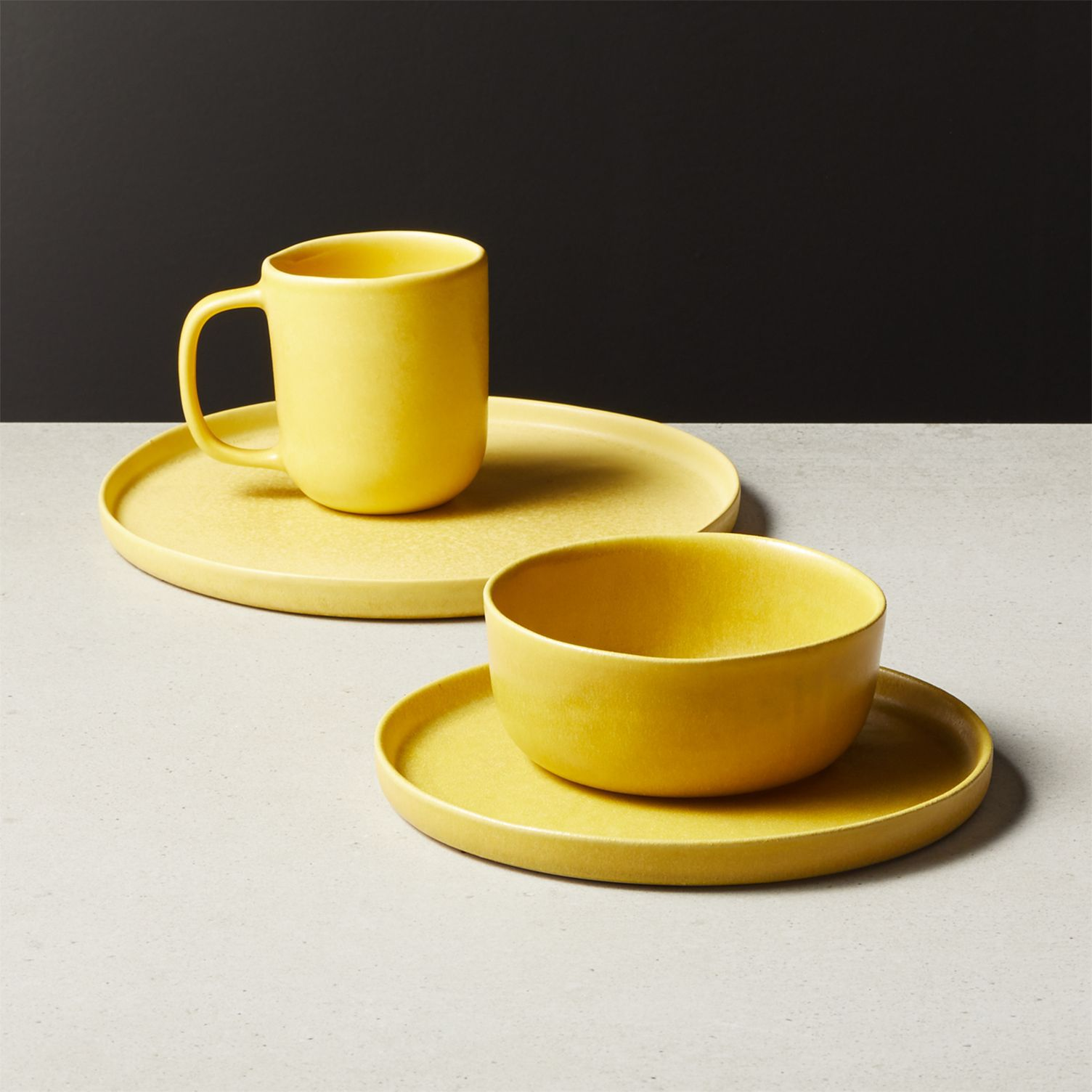 A four piece setting of yellow ceramic tableware by CB2.
