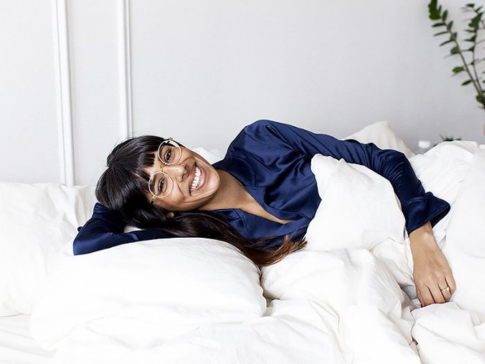 a happy woman laying in bed
