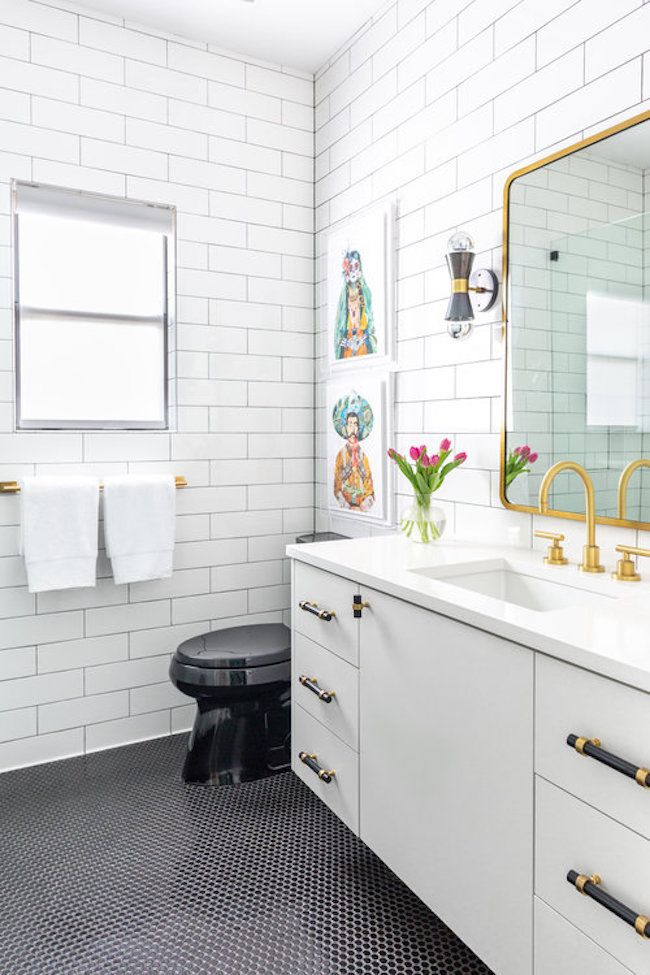 subway tile bathroom with gold mirror