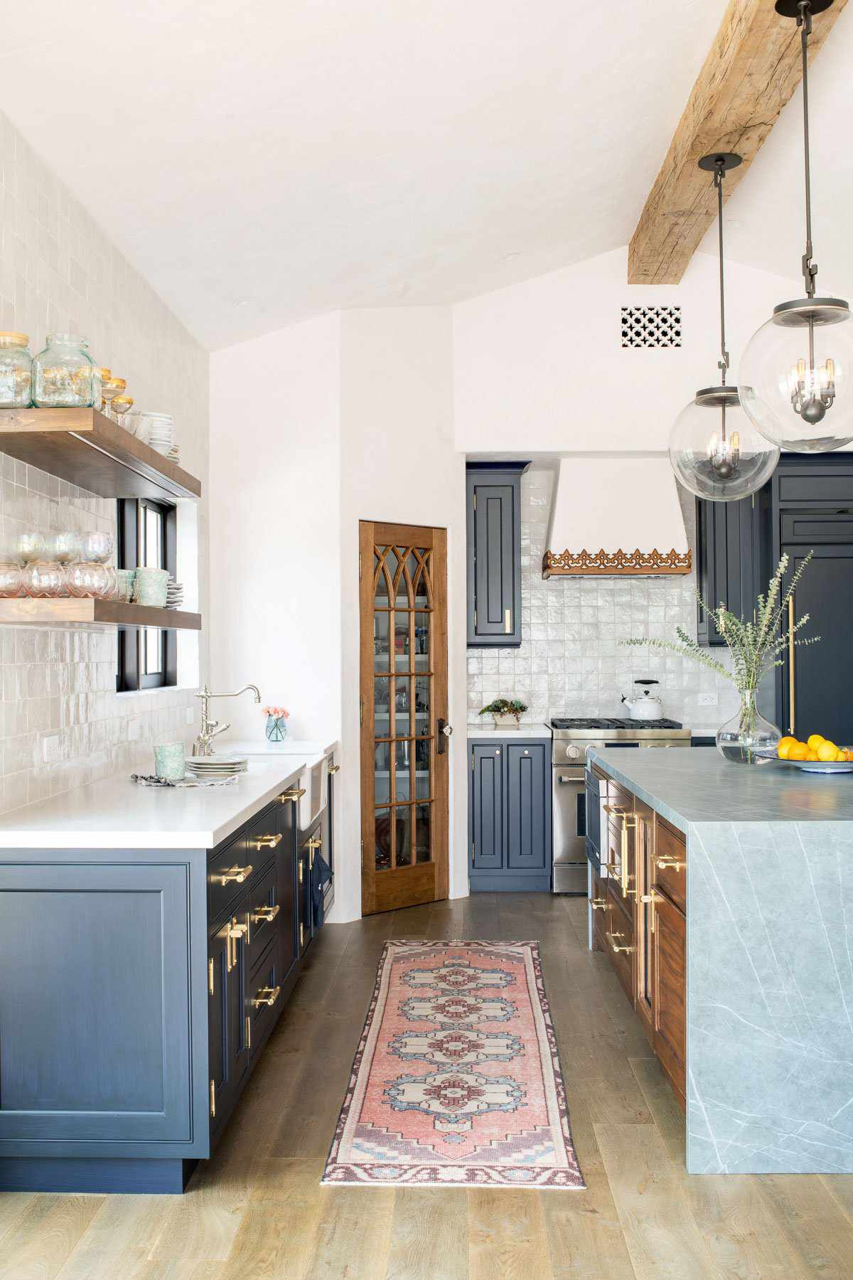 A vibrant kitchen with navy cabinets and a pink printed rug
