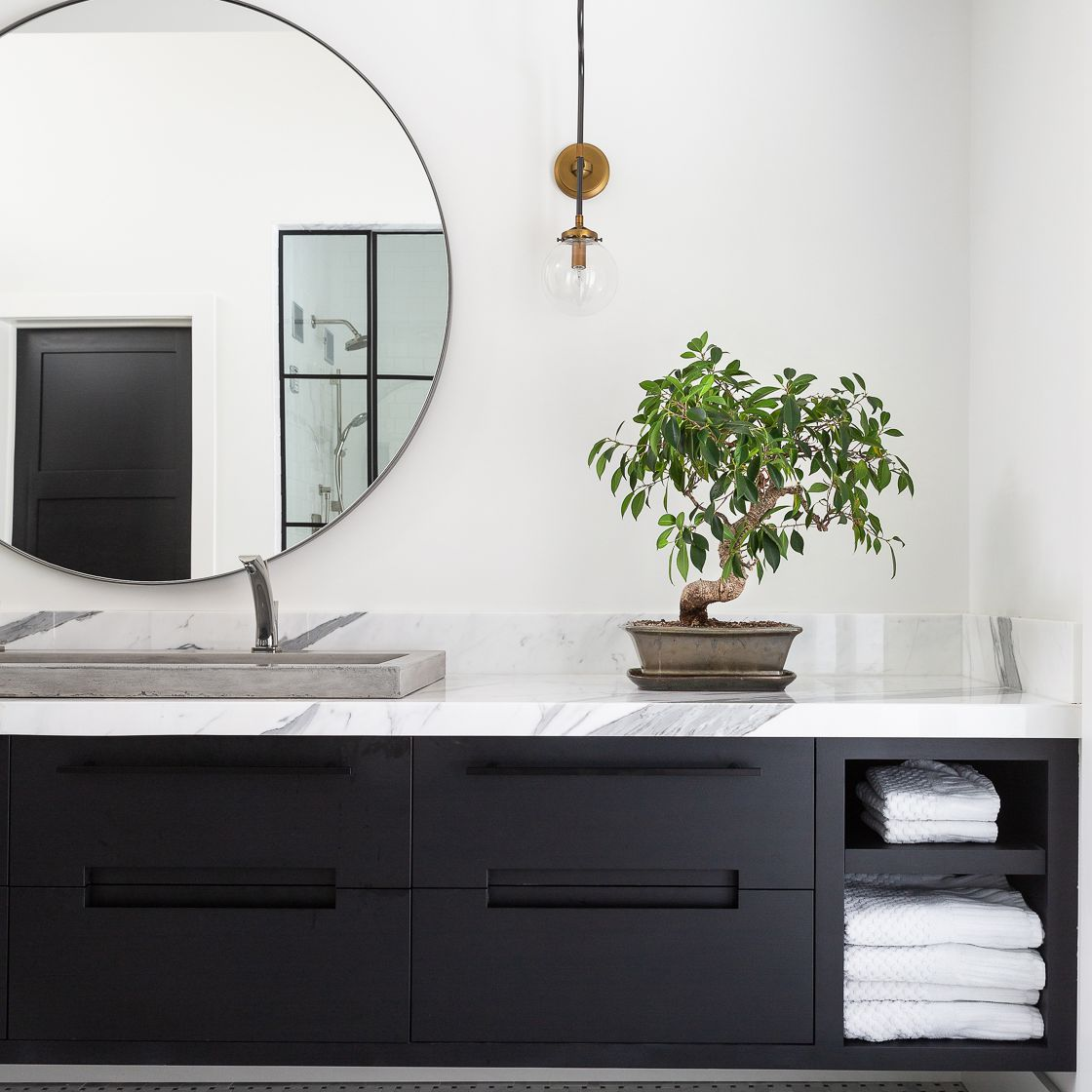 A bathroom lined with marble countertops and a built-in marble backsplash