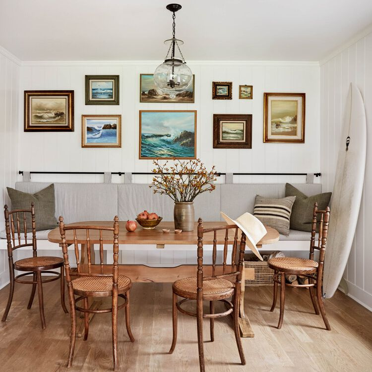 A dining room flanked by a gallery wall, which is comprised entirely of blue ocean paintings