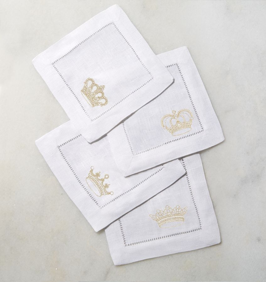 A set of four square linen cocktail napkins with a crown stitched into the corner of each one.