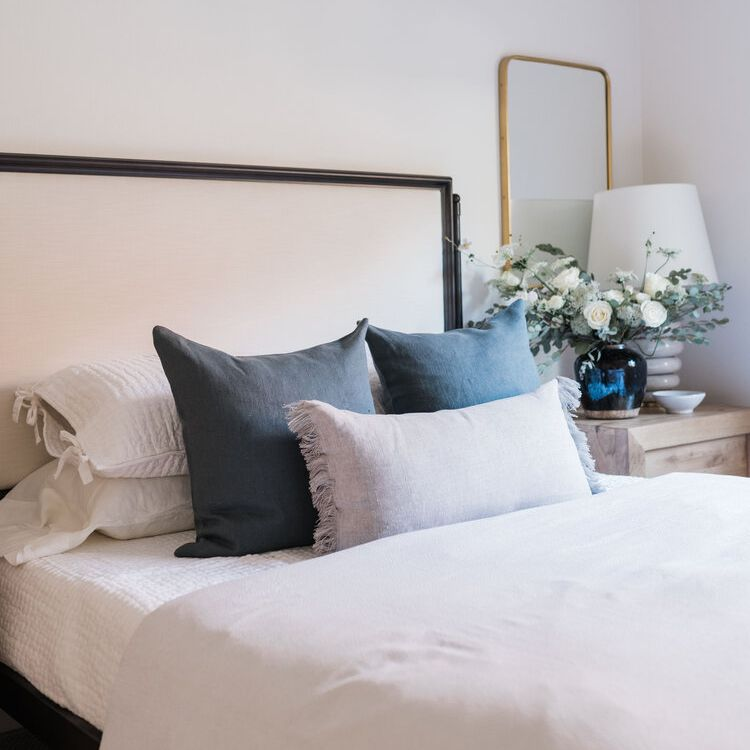 Neutral bed with linen pillows and wooden nightstand.