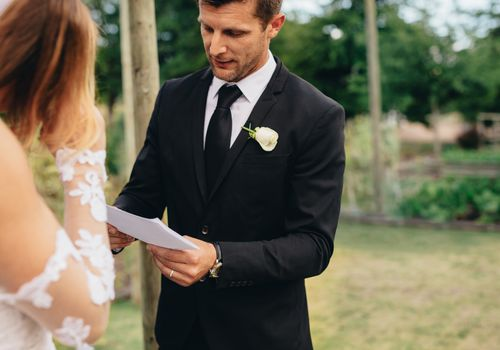Groom reading vows at ceremony