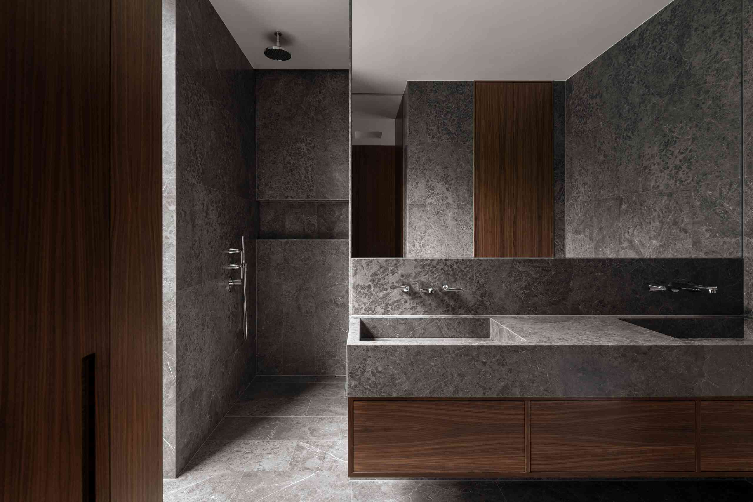 Gray stone and dark wood bathroom