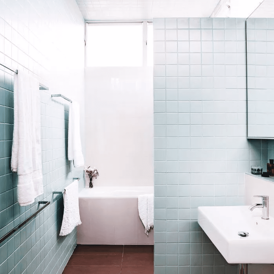 Pastel mint tiled bathroom with earth-toned floor