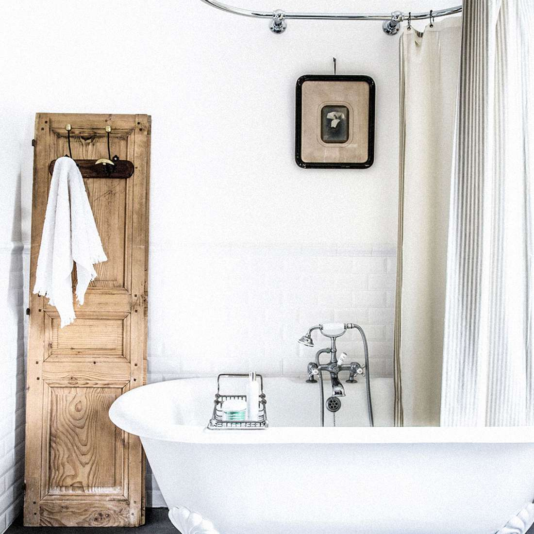 A bathroom with a clawfoot tub, a vintage photograph, and a towel rack made from an antique door