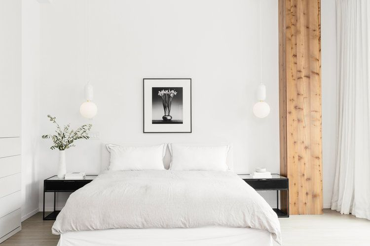 Scandinavian white bedroom with large exposed wooden beam.