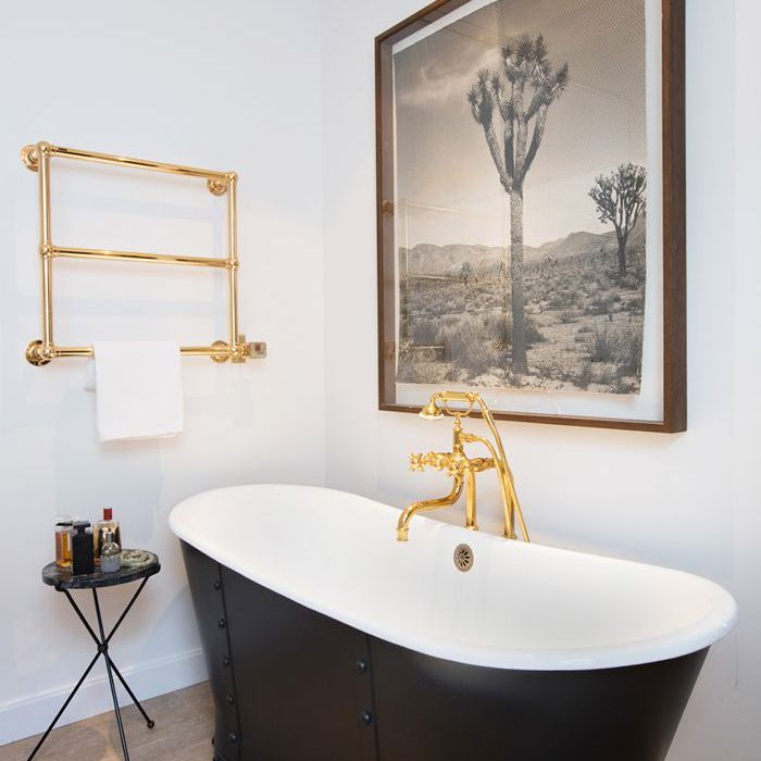 A large, framed print hangs above a bathtub next to gilded towel rack