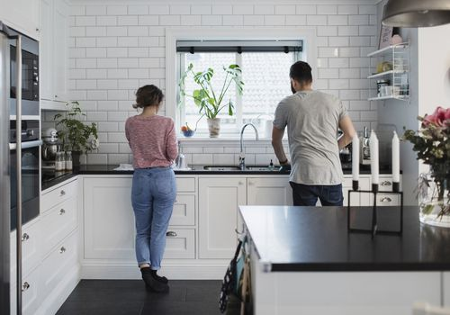 A woman and man doing the dishes in an all-white tiled kitchen.