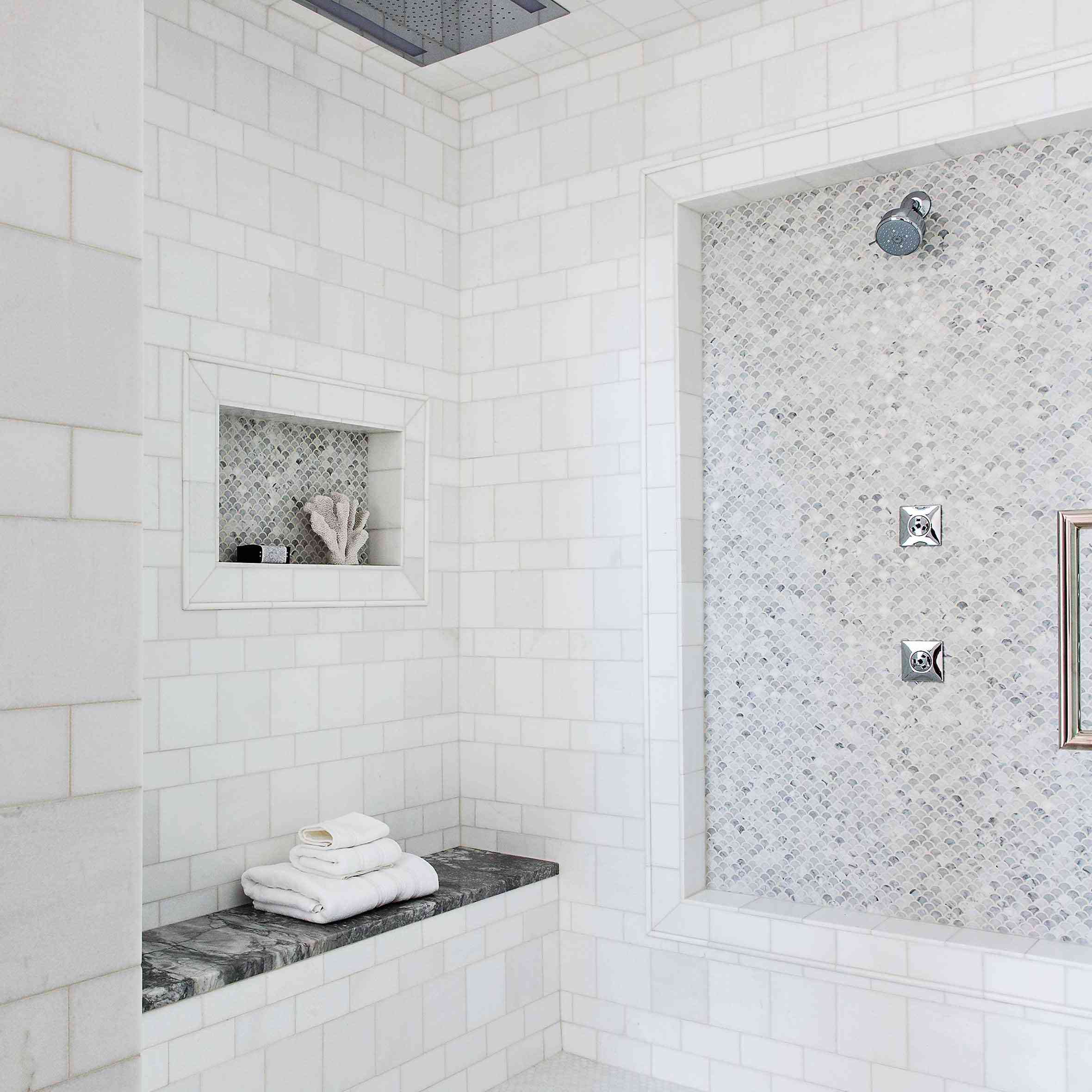 A shower lined with three different kinds of tile