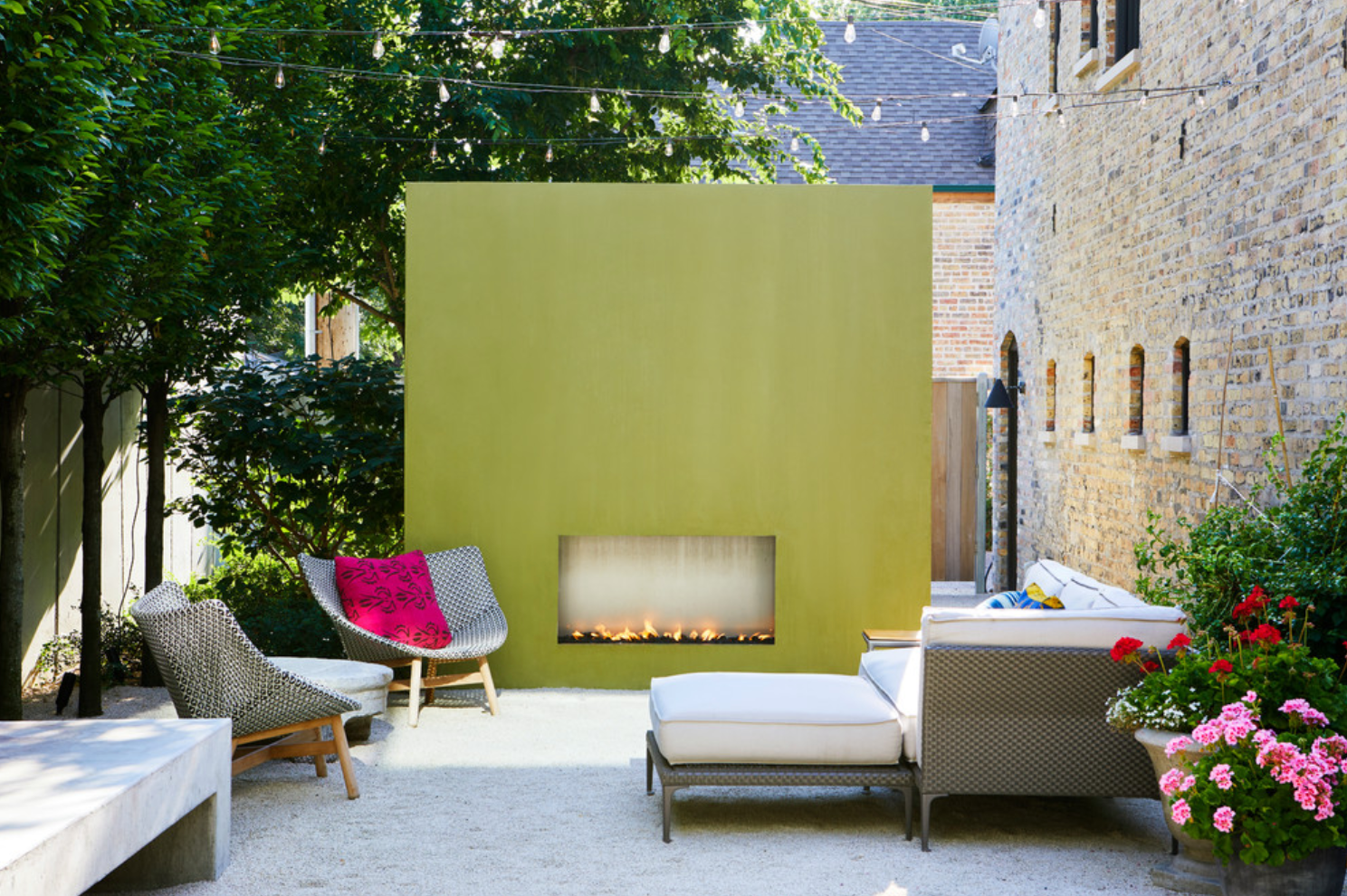 An outdoor space with several cozy seats and a large yellow fireplace