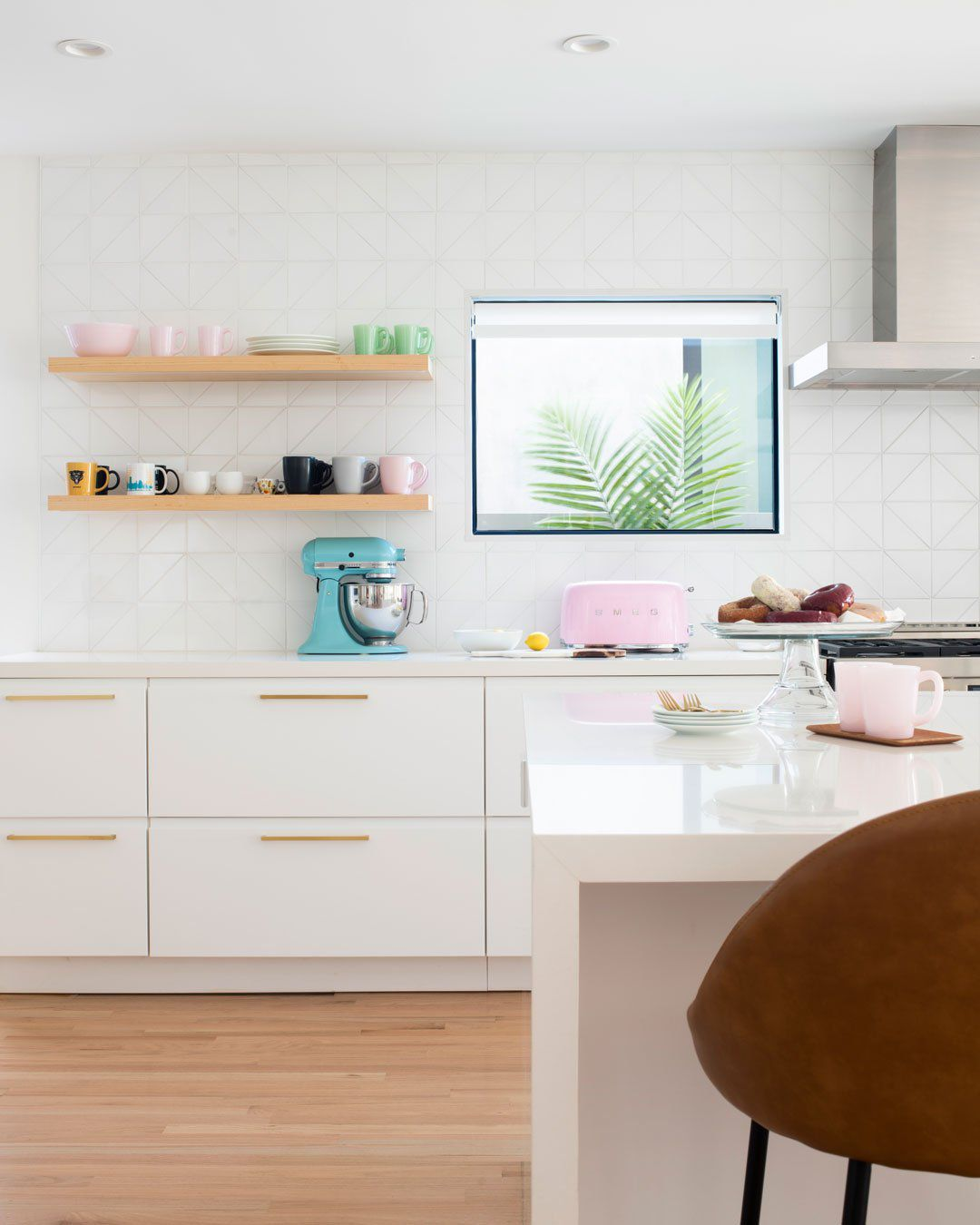 An all-white kitchen with a triangular tile-lined backsplash