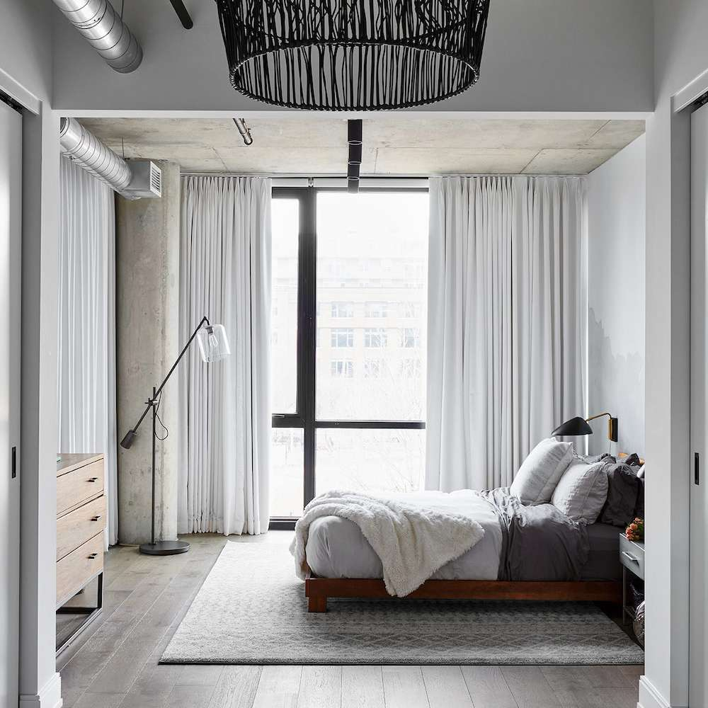 A light gray bedroom with white, black, and slate gray accents