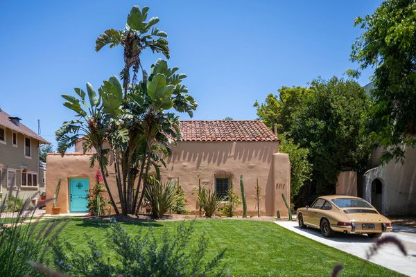 Unique adobe style house exterior with palm trees.