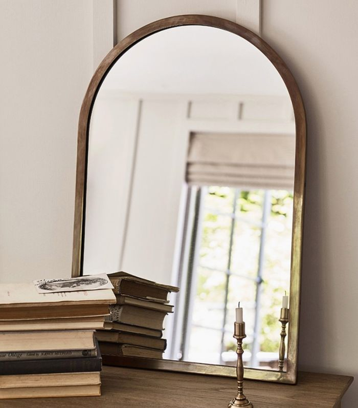 A wall mirror with a curved top edge and brass frame.