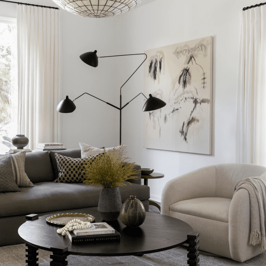 A living room with several geometric pieces of furniture and two striking light fixtures