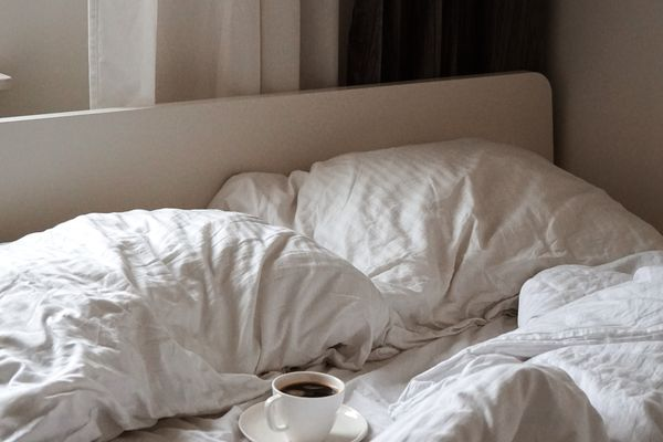 unmade bed with coffee cup on it