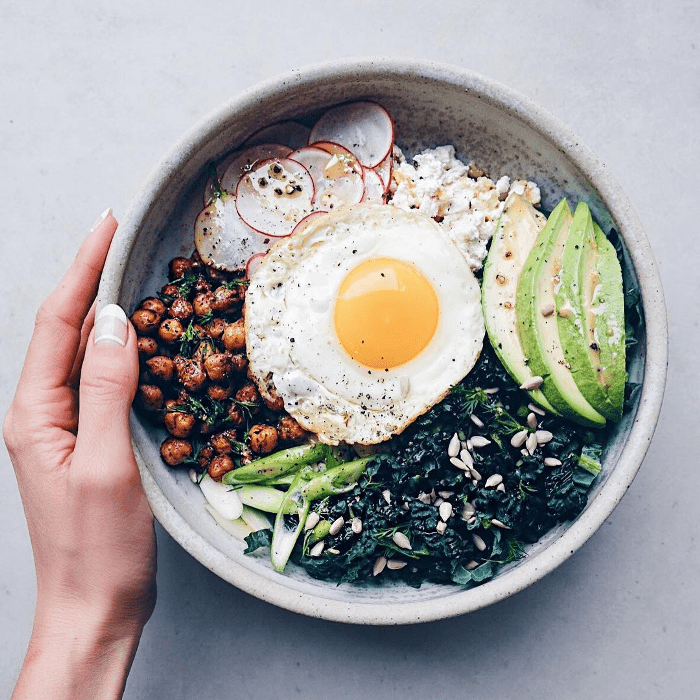 a gut-healthy bowl with greens, avocado, and a fried egg