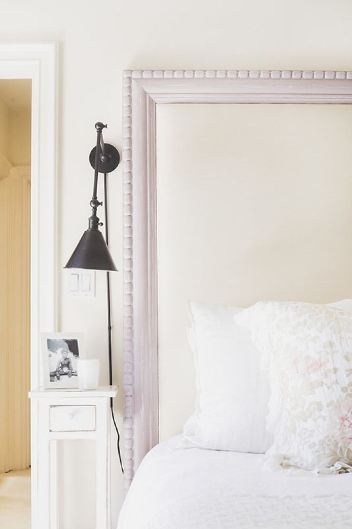 A bedroom with a white headboard that's been painted lavender along the trim