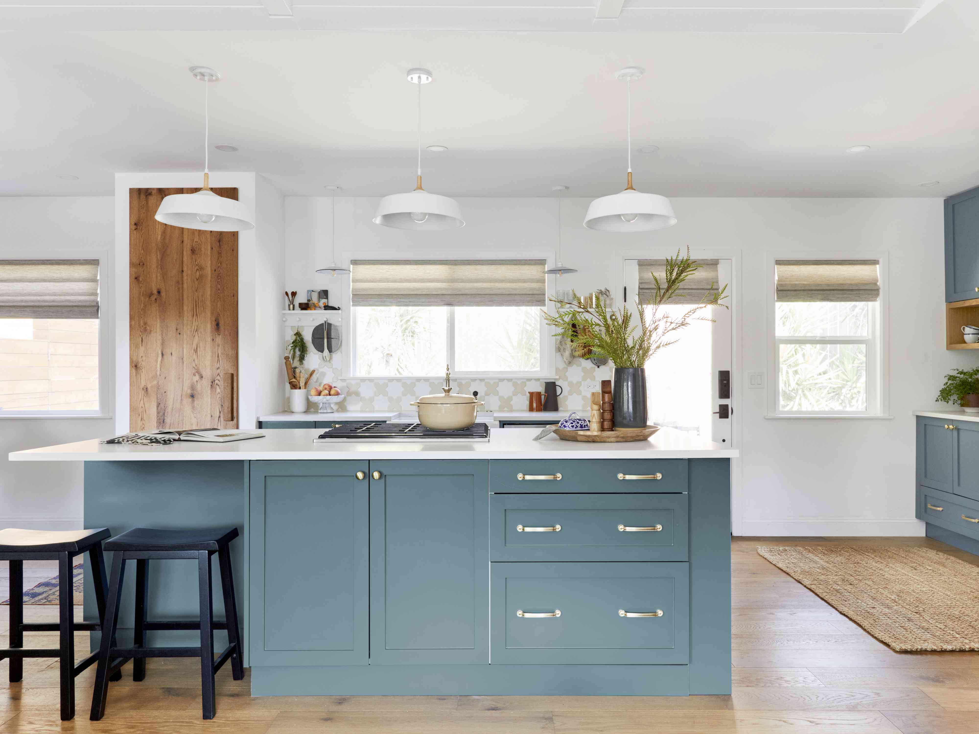 Teal kitchen island in white kitchen with white pendant lights.