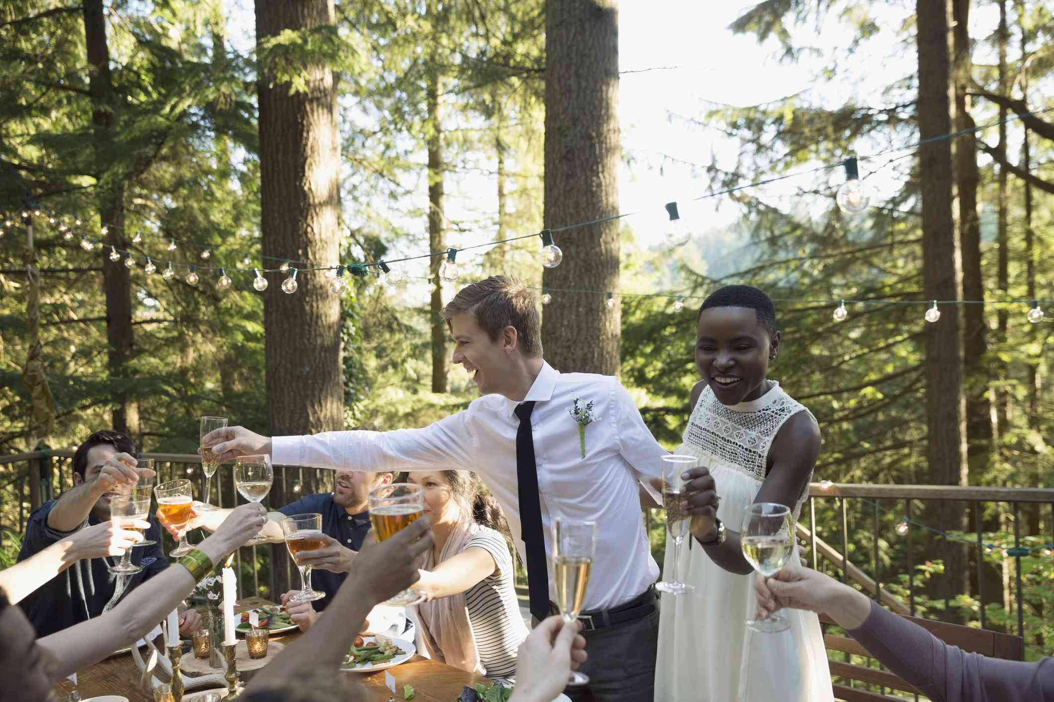 Young couple makes toast at outdoor wedding reception