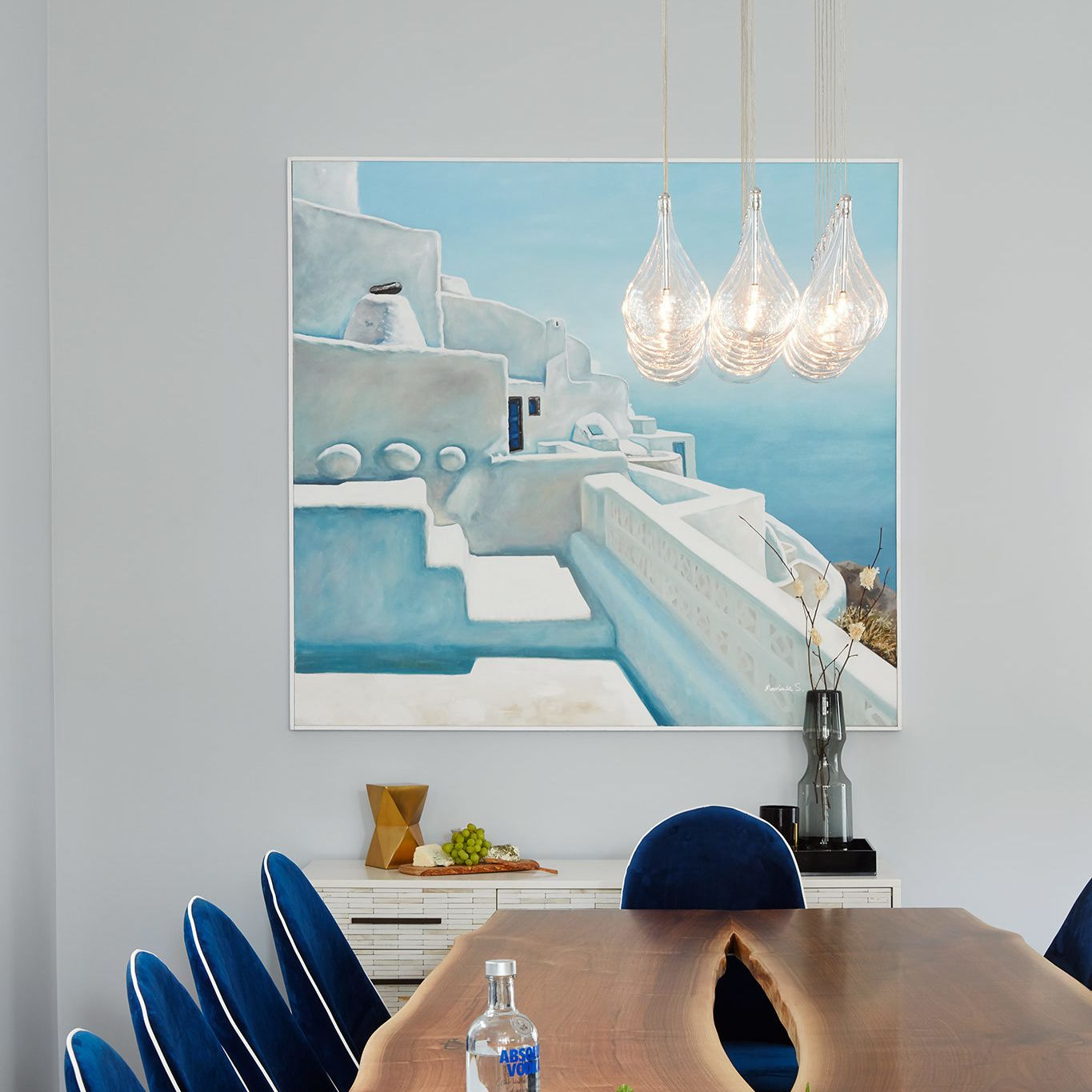A dining room decorated with navy upholstered chairs and a light blue painting