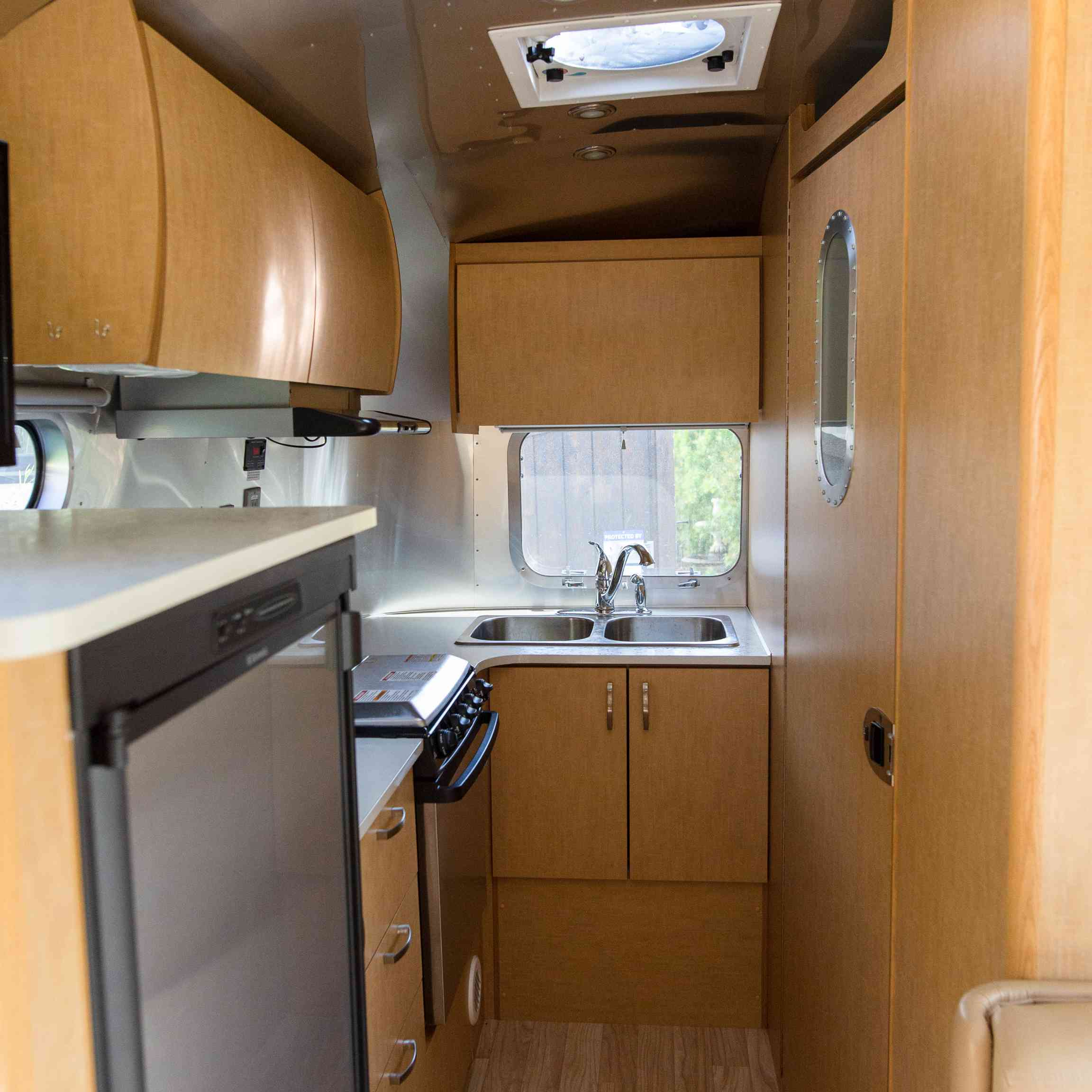 Tight inside of Airstream with oak cabinetry.