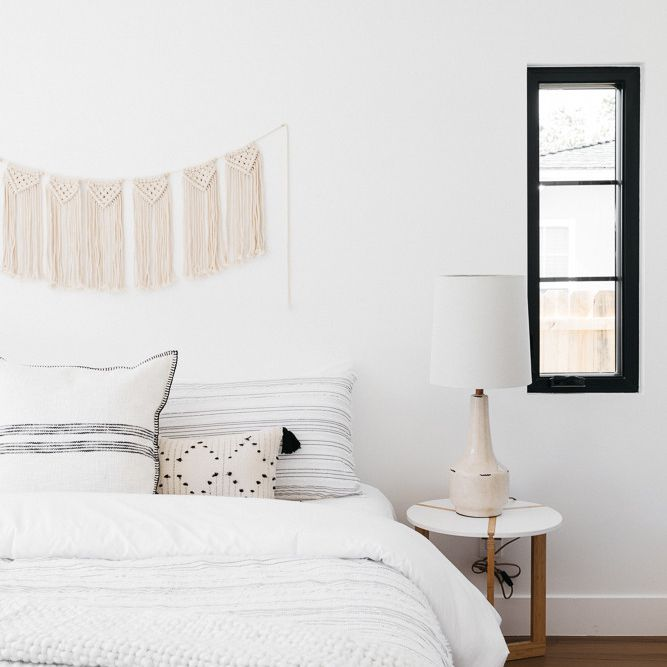 White bedroom with striped throw pillows