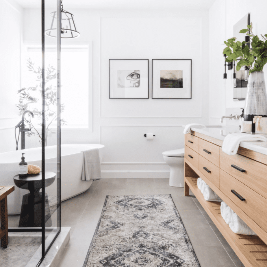A master bathroom with a gray printed rug lining the floors
