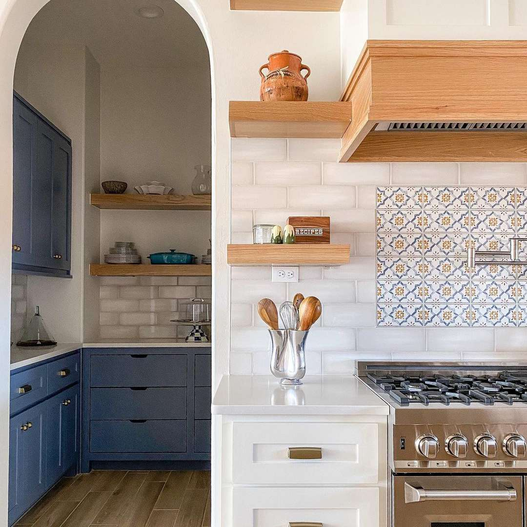 Kitchen with archway and blue and white cabinets.