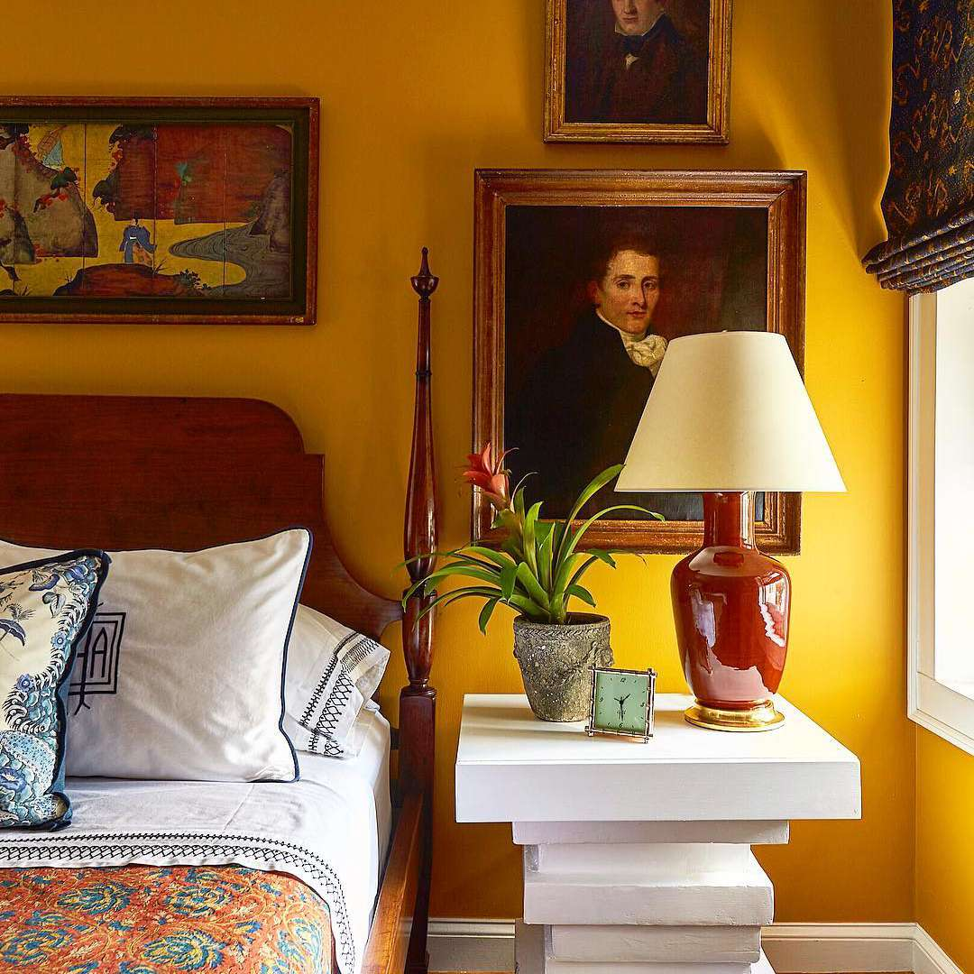 Yellow bedroom with framed art and sculptural nightstand