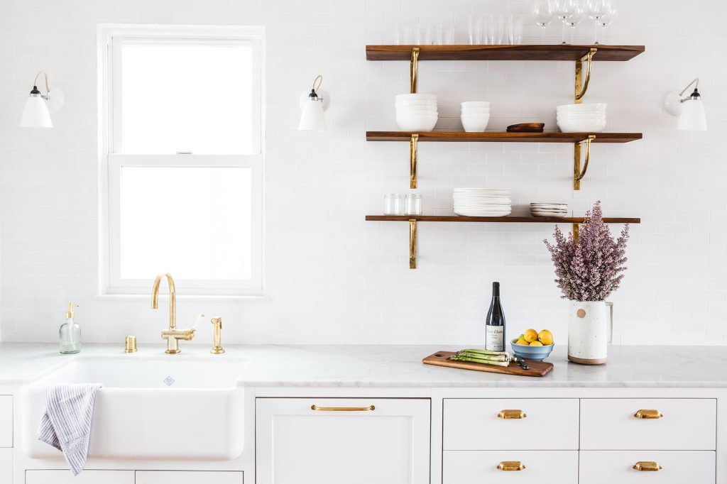 An all-white kitchen with a few wooden shelves